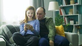 Een paar die samen een smartphone op de bank in zijn woonkamer gebruiken stock video