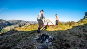 Een paar die een tent in de wildernis in Noorwegen opbouwen, dichtbij Preikestolen royalty-vrije stock foto's