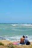 Een paar die toeristen op het strand door de Mistral wordt geveegd - Apulia stock fotografie