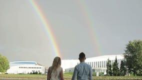 Een paar die van twee regenbogen in de hemel genieten stock videobeelden