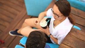 Een paar drinken een kerel en een meisje koffie en babbelen in een informele openluchtkoffie Snel voedsel stock video