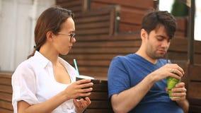 Een paar drinken een kerel en een meisje koffie en babbelen in een informele openluchtkoffie Snel voedsel stock videobeelden