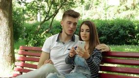 Een paar in een verhouding maakt selfie in het park op een bank stock video