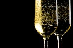 Een paar fluiten van champagne met gouden bellen op zwarte achtergrond Royalty-vrije Stock Foto