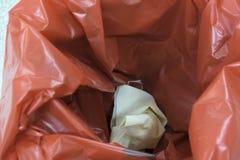 Een paar gebruikte handschoenen binnen een rode bak voor huisvuil royalty-vrije stock foto's