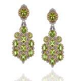 Een paar gele en witgoudoorringen met diamanten en groene saffieren Stock Afbeelding
