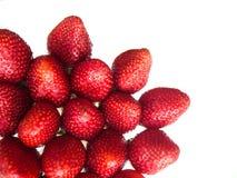 Een paar gezonde rode aardbeien in de lagere linkerhoek op een geïsoleerde achtergrond Stock Foto