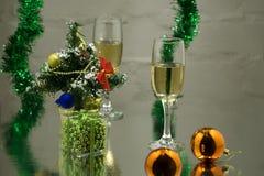 Een paar glazen met champagne op een houten lijst met Kerstmisballen, een rood lint met een twijg van sparren op donkere backgro Stock Afbeeldingen