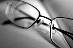 Een paar glazen op een boek in zwart-wit stock afbeelding