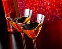 Een paar glazen van cocktail op barlijst voor flessen Stock Foto