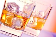 Een paar glazen van drank met ijs op disco violet licht Stock Fotografie