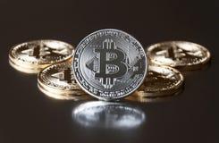 Een paar gouden en zilveren muntstukken bitcoin liggen of verblijf op rand op een donkere achtergrond Het concept crypto munt Stock Foto's