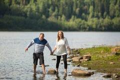 Een paar het lopen holdingshanden op de rivier stock foto's