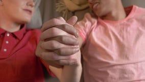 Een paar jonge multinationale homosexuals legt op de laag en holdingshanden Homeliness, homosexueel, liefde, jonge LGBT-familie stock footage