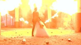 Een paar jonggehuwden bij een Halloween-partij, een reusachtige vlam flakkert omhoog dichtbij hen stock videobeelden