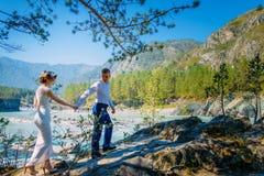Een paar jonggehuwden die op de rots in de wilde aard lopen In de achtergrond, het bos, de rivier en de bergen stock fotografie