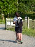 Een paar kerels berijden een elektrische autoped in het park Mening van de rug royalty-vrije stock foto's