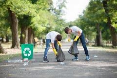 Een paar kleine jongens die zwarte vuilniszakken houden en plastic vuilnis op een parkachtergrond verzamelen ecologie stock foto's
