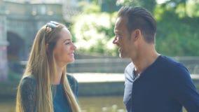 Een paar komt voor een datum op een de zomerdag samen op de rivier en heeft pret stock videobeelden