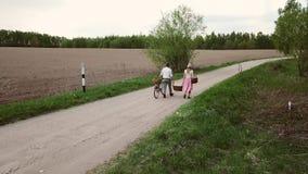 Een paar landbouwers met een fiets draagt manden langs de weg in het dorp stock footage