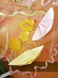 Een paar lichte document schepen met zeilen van gele bladeren op een gele die okerachtergrond, met pastelkleurkleurpotloden worde royalty-vrije stock afbeelding