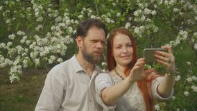 Een paar in liefde bekijkt foto's op het smartphonescherm en neemt een selfie stock video