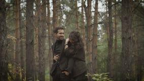 Een paar in liefde in het bos het begin van de herfst, het bos in zijn boete Het meisje koestert de haar mens Zij omhelzen en stock videobeelden