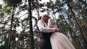 Een paar in liefde koestert in een mooi pijnboombos het meisje in de witte kleding die tegen haar vriend wordt geleund en zette h stock footage