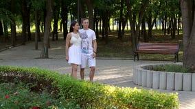Een paar in liefde loopt in het park in de zomer stock video