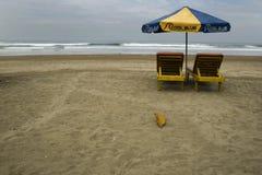 Een paar ligstoelen en luifel in het strand van Kuta Bali stock fotografie