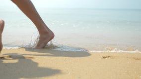 Een paar loopt langs het strand op een duidelijke zonnige dag Zij houden handen en kus de voeten mannen en vrouwen het lopen stock video