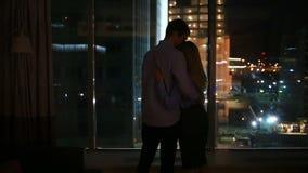 Een paar mannen en vrouwen die in een groot venster in een nachtstad kijken omhels stock videobeelden