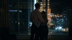 Een paar mannen en vrouwen die in een groot venster in een nachtstad kijken omhels stock footage