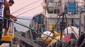 Een paar mensen in haven visserij stock videobeelden