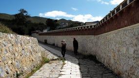 Een paar mensen lopen langs kleine steenstraat stock afbeelding