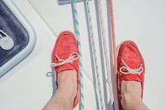 Een paar mensenbenen in topsiders op wit jachtdek yachting royalty-vrije stock foto's
