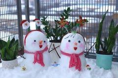 Een paar mooie kleine sneeuwmannen wordt opgestapeld op het balkon stock fotografie