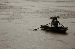Een paar ontsnapt aan de zware regen op een boot in Central Park in New York stock foto's