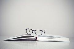 Glazen op boek Stock Fotografie