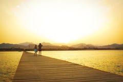 Een paar op de houten pijler bij zonsondergang royalty-vrije stock foto