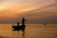 Een paar op hun vissersboot die in de ochtend werken Stock Foto's
