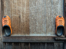 Een paar oranje rubberpantoffels op oude houten Royalty-vrije Stock Afbeeldingen