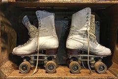 Een paar oude, retro, lace-up rolschaatsen bevindt zich insdie een houten doos stock foto's