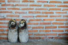 Een paar oude schoenen op bakstenen muurachtergrond, oude achtergrond, oude laarzen Royalty-vrije Stock Foto
