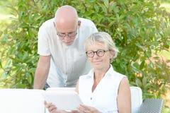 Een paar oudsten bekijken een digitale tablet stock afbeeldingen