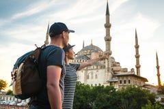 Een paar reizigers dichtbij de wereldberoemde Blauwe Moskee in Istanboel, Turkije Het meisje toont richting stock afbeeldingen
