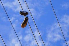 Een paar schoenen op Elektrodraadtoren Stock Fotografie
