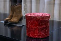 Een paar schoenen van vrouwen en een glanzende rode doos op de supermarkt demonstreren Het concept vakantie verkoop of het winkel stock fotografie