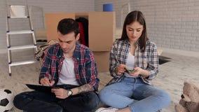 Een paar tellend geld en het neerschrijven van hun uitgaven in blocnote housewarming stock videobeelden