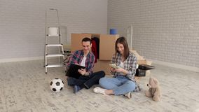 Een paar tellend geld en het neerschrijven van hun uitgaven in blocnote housewarming stock footage